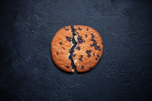 黒い背景にチョコレートを入れた 2 つの壊れた 1 つのクッキー 碑文の画像