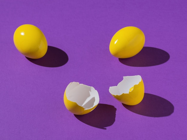 One broken and two whole yellow eggs on a purple background.