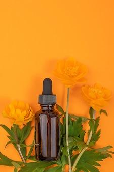 美容液、エッセンシャルオイル、その他の化粧品とオレンジ色の花が入った茶色のガラス瓶1本