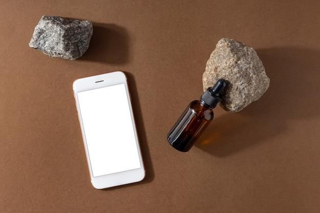 茶色の背景にピペットと携帯電話のモックアップ、石と技術の組成物が付いた茶色の血清ガラス瓶1本。ナチュラルオーガニックスパ化粧品コンセプト上面図