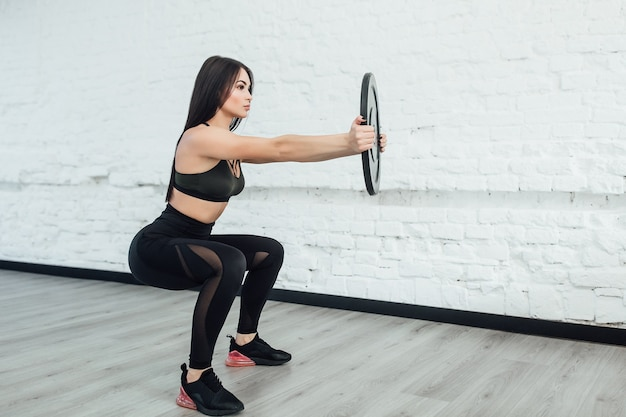 One, brunette caucasian woman exercising fitness body building exercises in studio. copy space.