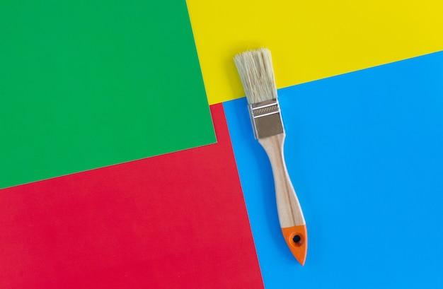 아파트나 집의 벽을 칠하기 위한 하나의 브러시. 배경 여러 가지 빛깔된 종이에 브러시. 아파트, 예술 및 미술 치료를 개조하는 개념.