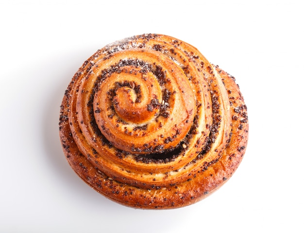 One bun with poppy seeds isolated on white surface.