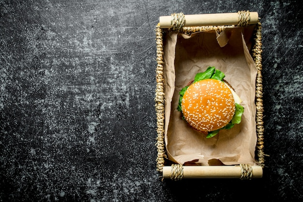 One burger in the basket. on black rustic background