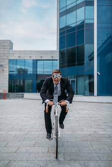 One businessman in funny glasses poses on bicycle at the office building in downtown. business person riding on eco transport on city street