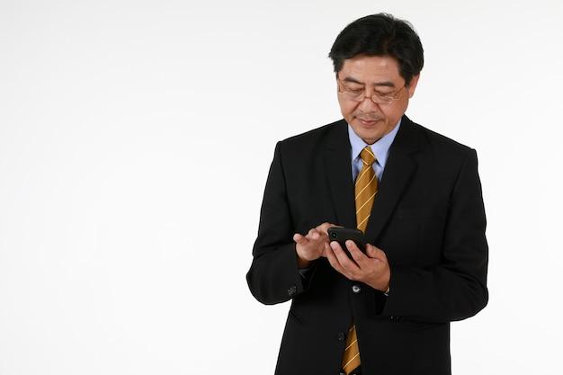 검은 정장을 입은 한 사업가가 서서 스마트폰 화면을 손에 들고 있습니다. 흰색 배경으로 스튜디오 촬영입니다. 투자, 뉴스, 기술, 미래에 대한 개념.