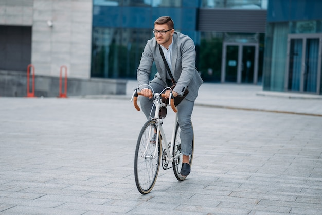 One businessman poses on bicycle at the office building in downtown. business person riding on eco transport on city street