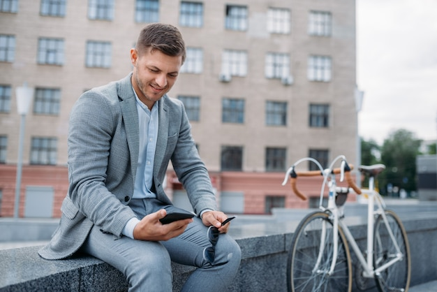 한 사업가 시내에 건물 사무실에서 자전거와 함께 포즈. 도시 거리에 에코 전송을 타고 비즈니스 사람