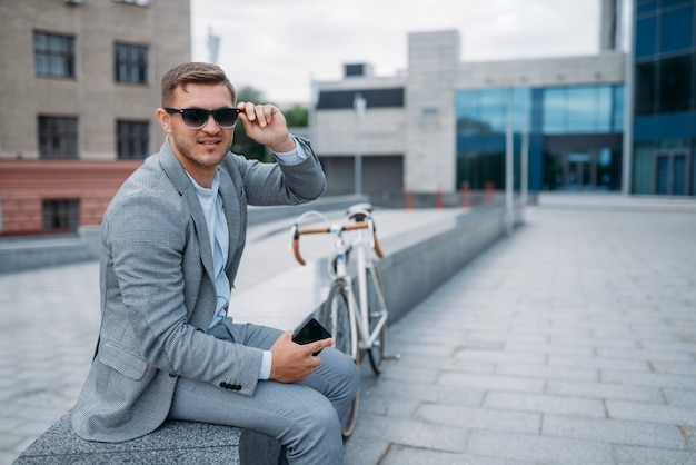 One businessman in sunglasses poses on bicycle at the office building in downtown. business person riding on eco transport on city street