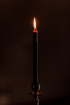 One candle burning at night on the black. candle isolated in black. close-up. selective focus