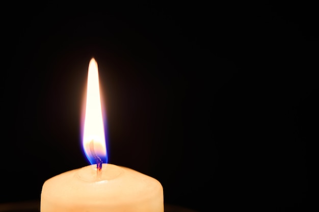 One candle flame in night dark