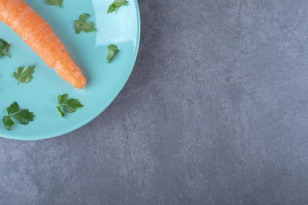 Una carota sul piatto con le verdure, sulla superficie di marmo.