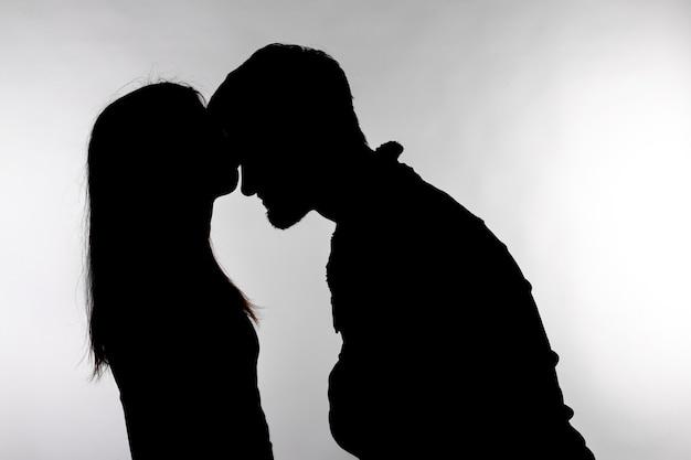 1人の白人カップルの男性と女性が白で隔離のスタジオシルエットでキス