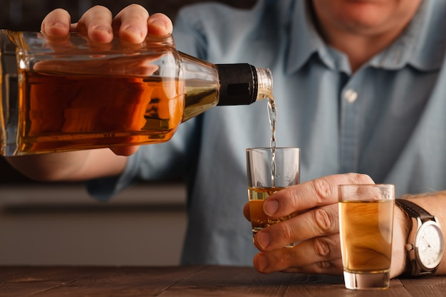 One caucasian man hands close up pouring alcohol in a glass