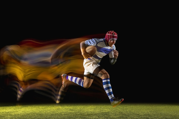 One caucasian man playing rugby on the stadium in mixed light. fit young male player in motion or action during sport game. concept of movement, sport, healthy lifestyle.