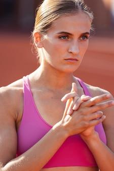 한 백인 여성 여성 운동선수 주자, 공공 경기장에서 혼자 연습