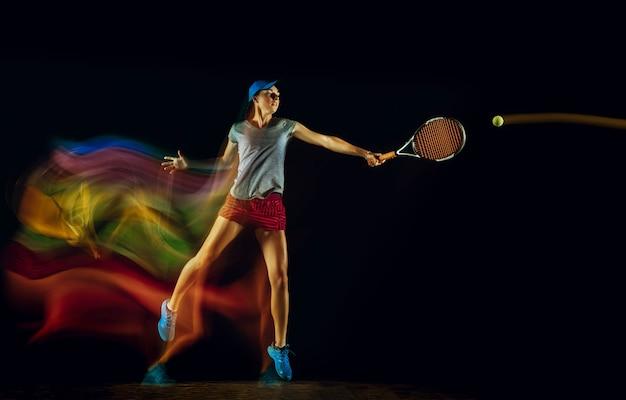 Una donna caucasica che gioca a tennis isolata sulla parete nera nella luce mista e stobe. montare la giovane giocatrice in movimento o in azione durante il gioco sportivo. concetto di movimento, sport, stile di vita sano.