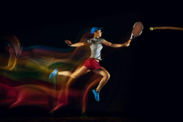 混合光とストーブ光の中で黒い壁に隔離されたテニスをしている白人女性。スポーツゲーム中に若い女性プレーヤーの動きや行動に合わせます。動き、スポーツ、健康的なライフスタイルの概念。