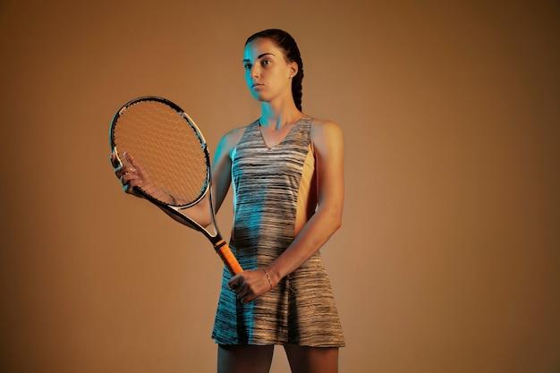 混合とネオンの光の中で茶色の背景に分離されたテニスをしている白人女性。スポーツゲーム中に若い女性プレーヤーを動かしたり行動させたりします。動き、スポーツ、健康的なライフスタイルの概念。