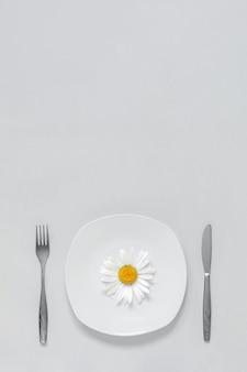 皿にカモミールの花1つ、灰色の背景にカトラリーフォークとナイフコンセプトベジタリアン健康的な食事療法または食欲不振。トレンディな色2021。