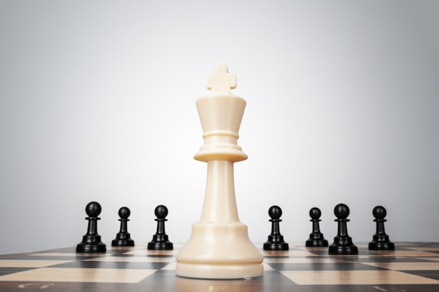 One chess pieces staying against thel set of chess pieces. strategy, business concept