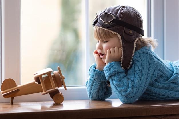 屋内でヴィンテージの木製飛行機で遊んでいる一人の子供