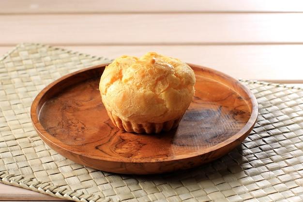木製プレートに1つのシュークリーム。シュークリーム、エクレア、シュークリーム、またはキューソーとして人気があり、ミルキークリームが入っています。