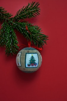 One christmas tree ball toy hanging on a coniferous spruce branch close-up.