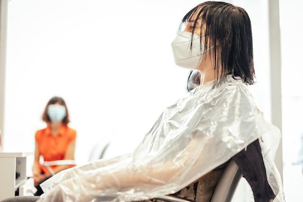カットを待っているマスクを持つ1つのクライアント。 covid-19パンデミックにおける美容院のセキュリティ対策を再開