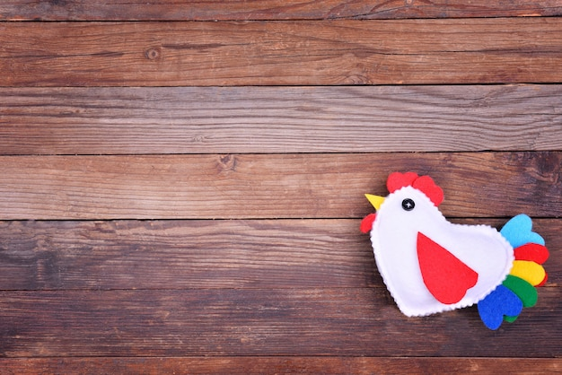 One cock on wooden brown background