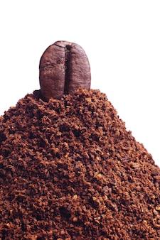 白で隔離される1つのコーヒー豆と挽いたコーヒーのクローズアップ