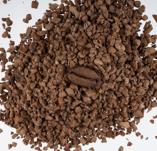 白い背景の上の挽いたコーヒーの山に1つのコーヒー豆。コーヒー豆の上面図