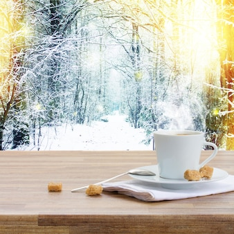 One coffee cup on wooden table, winter scenery in background