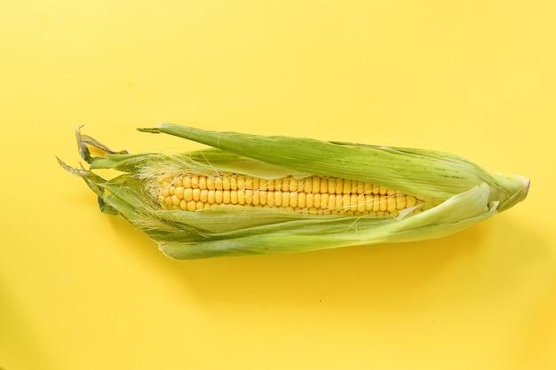 黄色の背景に1つのトウモロコシ最小限の食品コンセプト上面図