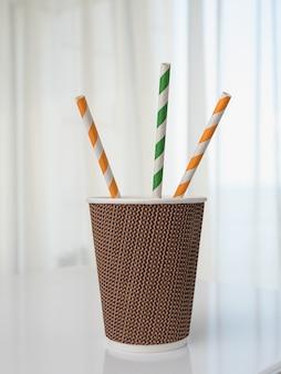 白いテーブルに3本の飲用チューブが付いたコーヒーツーゴー用の1つの段ボールテクスチャガラス