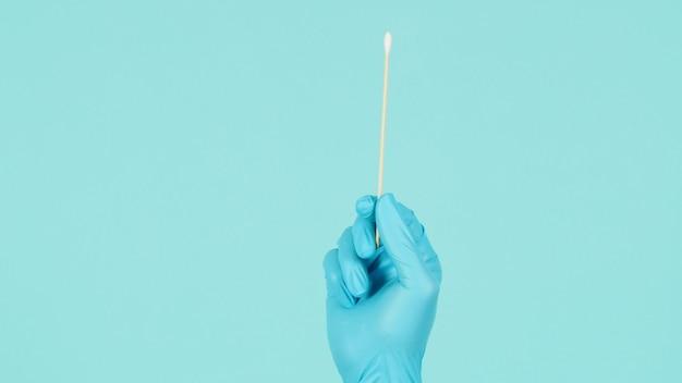 파란색 의료용 장갑이나 민트 그린 또는 tiffany blue background.covid-19 개념의 라텍스 장갑과 함께 손에 면봉 테스트를 위한 면봉 1개. 확대