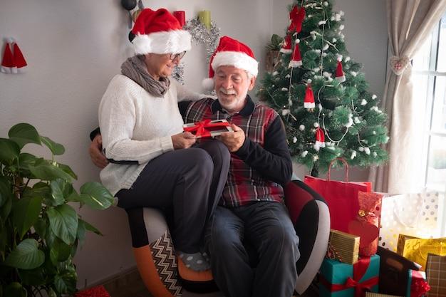 산타 모자를 쓰고 같은 안락의자에 함께 앉아 있는 노인 부부. 크리스마스 선물로 받은 태블릿을 들고. 백그라운드에서 선물과 크리스마스 트리