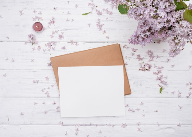 One craft envelop, white paper on it, lilac and purple candle on old white wooden background