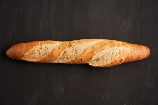 One crispy french baguettes lie dark black table background