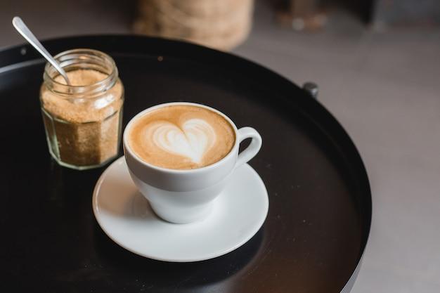 Одна чашка капучино с латте-артом на черном столе, белая керамическая чашка, вид сверху. кафе-культура.