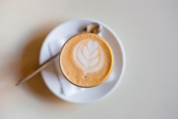 Одна чашка капучино с латте-артом на белом деревянном столе, белая керамическая чашка, вид сверху. кафе-культура.