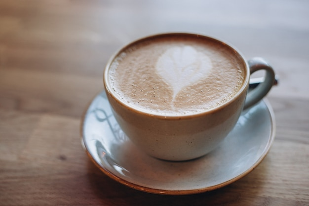 Одна чашка капучино с латте-артом на деревянном столе, белая керамическая чашка. кафе-культура.