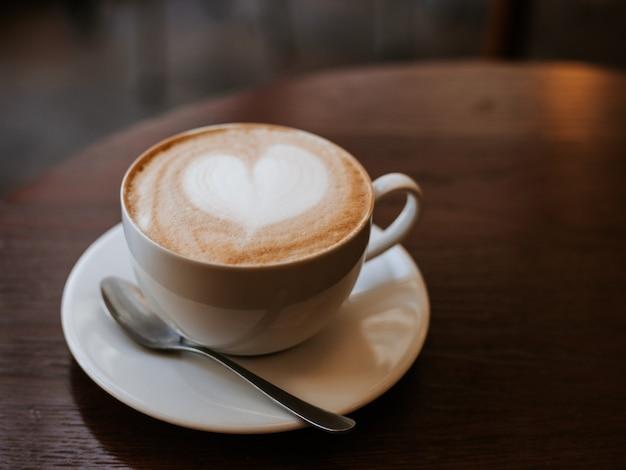 Одна чашка капучино с латте-артом на деревянном столе, белая керамическая чашка, место для текста. кафе-культура.