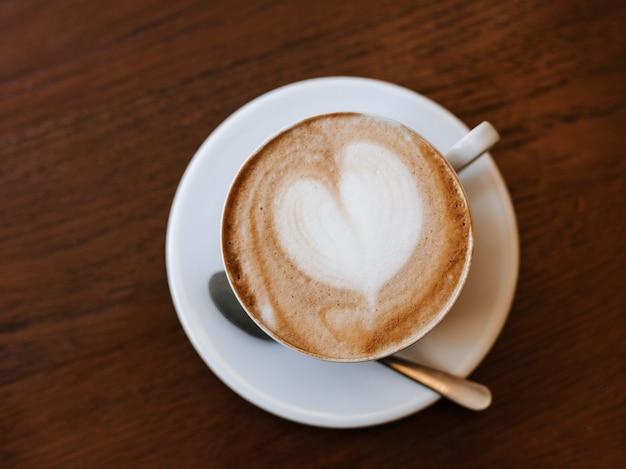 Одна чашка капучино с латте-артом на деревянном столе, белая керамическая чашка, вид сверху. кафе-культура.