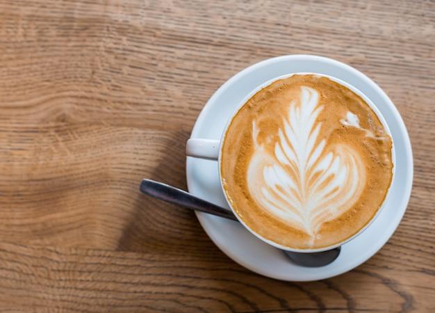 Одна чашка капучино с искусством латте на деревянный стол, белая керамическая чашка, вид сверху. кафе культуры.