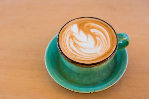 Одна чашка капучино с латте-арт на деревянном столе