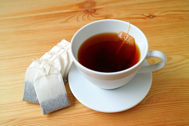 나무 테이블에 티백과 갓 양조 뜨거운 차 한 잔