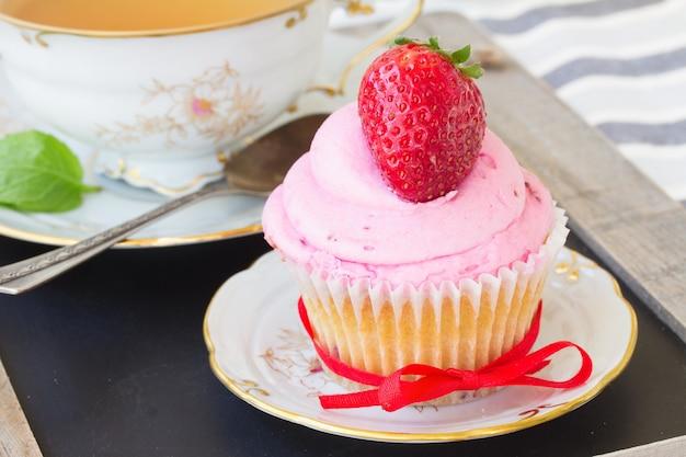Один кекс со свежей клубникой в тарелке на деревянном столе