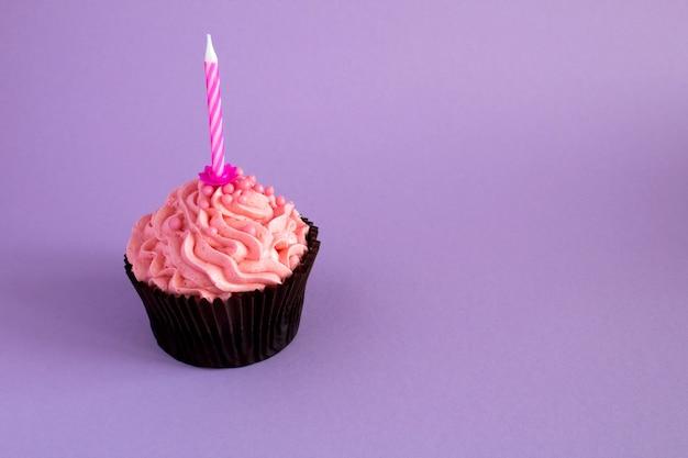 ピンクのクリームとバイオレットのキャンドルで1つのカップケーキ