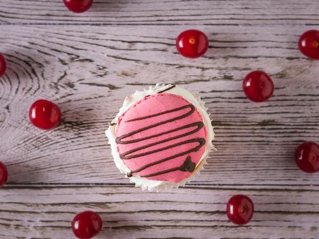 Один кекс со спелой вишней на столе. плоская планировка. десерт из свежих ягод вишни.